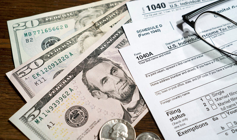 dollar bills and tax forms