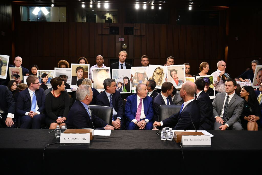 "Family members hold up photos of loved ones they lost, as John Hamilton(L), vice president and chief engineer of Boeing Commercial Airplanes and Dennis Muilenburg(R), president and CEO of the Boeing Company speaks during a full committee hearing on ""Aviation Safety and the Future of Boeing's 737 MAX"" on Capitol Hill."