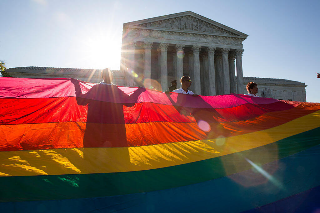 Supporters of same-sex marriage unfurl a large rainbow pride flag near the Supreme Court, April 28, 2015 in Washington, DC. On Tuesday the Supreme Court will hear arguments concerning whether same-sex marriage is a constitutional right, with decisions expected in June.