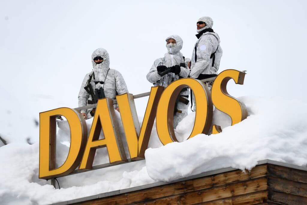 "Security stand on a rooftop next to letters reading ""Davos"" surrounded by snow"