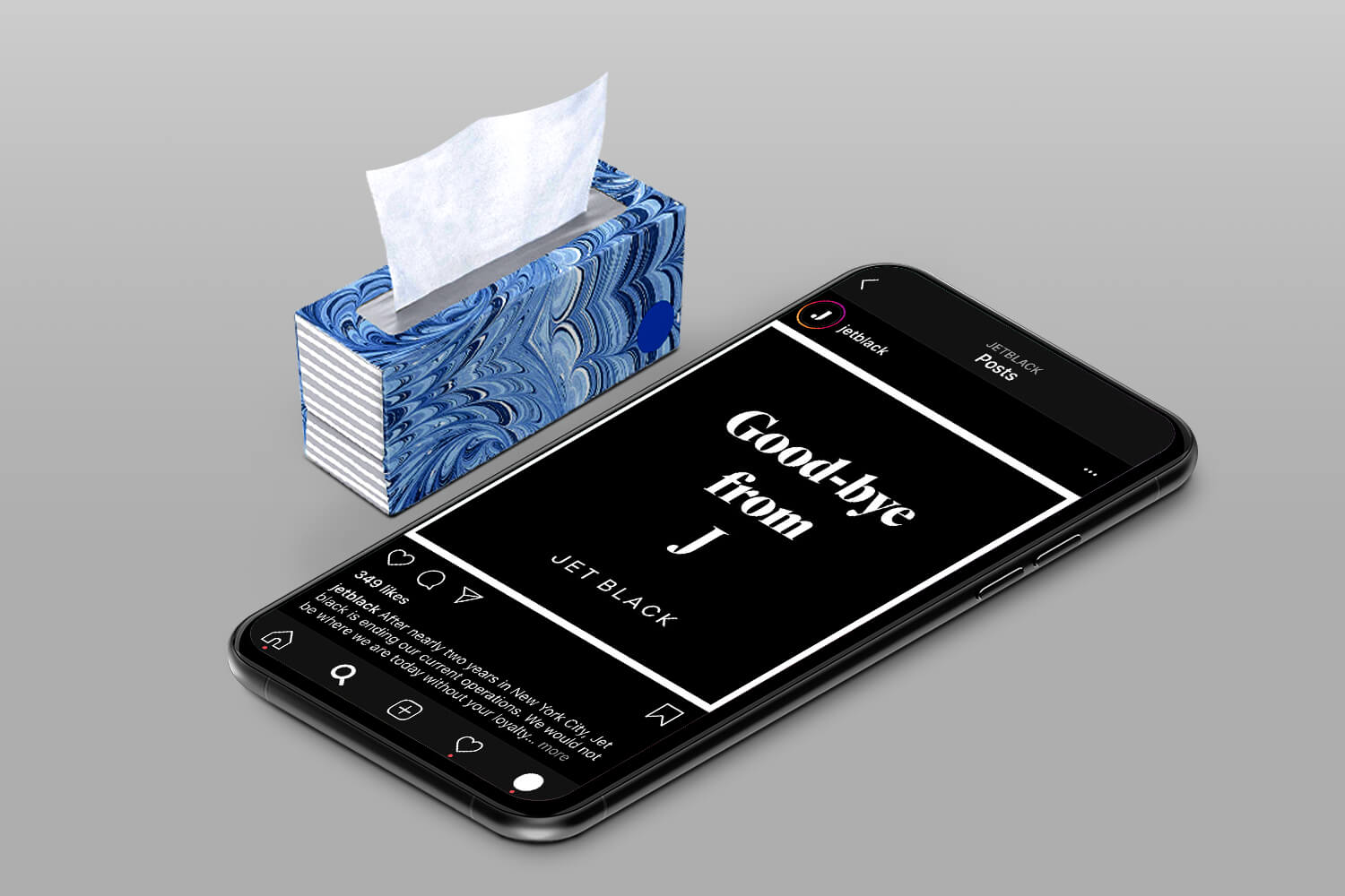 A phone open to a JetBlack screen next to a box of tissues