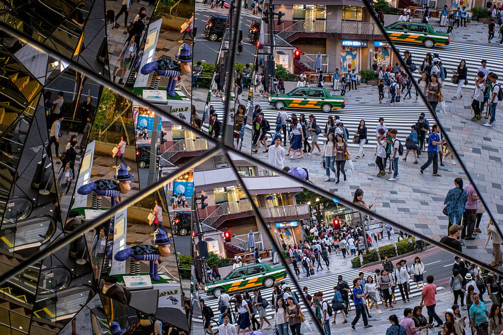 People are seen reflected in a shopping mall mirror at a busy intersection in the shopping district of Harajuku on June 18, 2015 in Tokyo, Japan